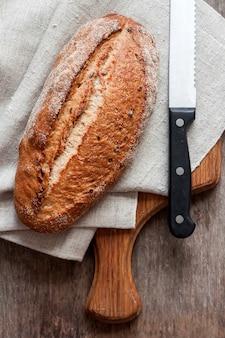 Pão integral de tábua de madeira na mesa da cozinha