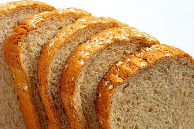 Pão integral fatiado em fundo branco.
