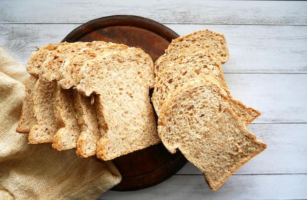 Pão integral fatiado em madeira branca