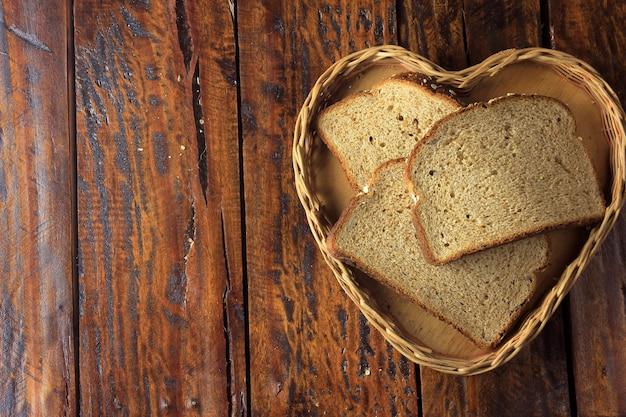 Pão integral fatiado orgânico dentro da cesta do coração da forma