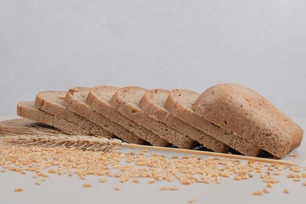 Pão integral fresco fatiado com grãos de aveia no fundo branco. foto de alta qualidade