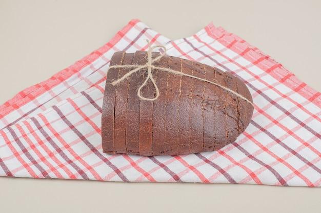 Pão integral fresco fatiado em corda na toalha de mesa