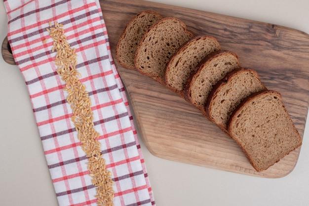 Pão integral fresco fatiado em tábua de madeira