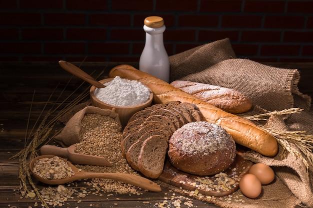 Pão integral inteiro, leite, farinha e saco de pano na tabela de madeira copie o espaço.