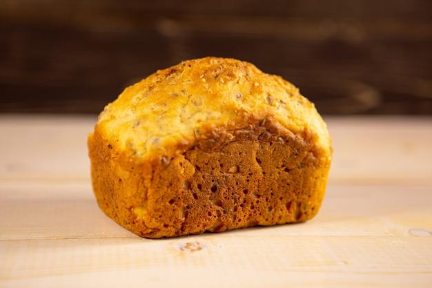 Pão integral recém-assado quente com crosta crocante em um fundo de madeira