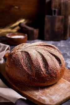 Pão integral redondo em uma tábua de madeira polvilhado com farinha e espigas de cereais em uma mesa escura