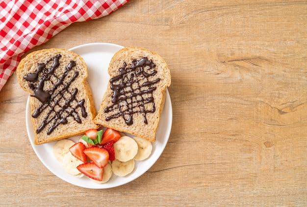 Pão integral torrado com banana fresca, morango e chocolate no café da manhã