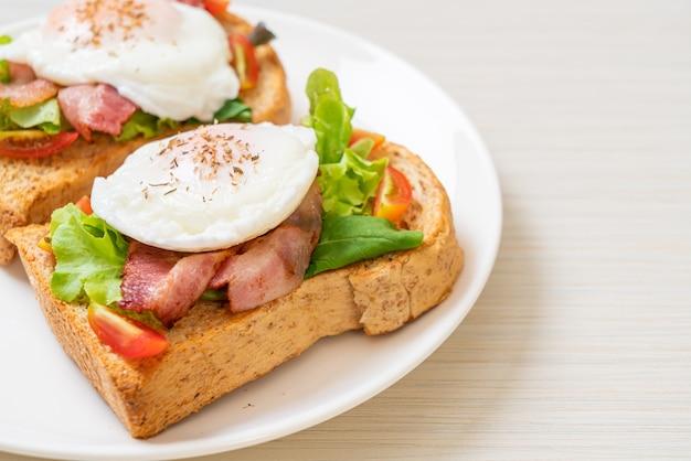 Pão integral torrado com vegetais, bacon e ovo ou ovo benedict no café da manhã