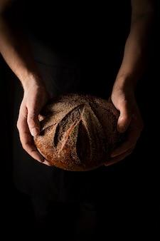Pão inteiro redondo nas mãos do padeiro em fundo preto com espaço livre para texto, foto vertical de humor escuro. foto de alta qualidade