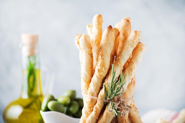 Pão italiano com sementes de gergelim e ervas em um fundo claro, foco seletivo, orientação horizontal