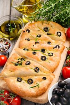 Pão italiano do focaccia com azeitonas e alecrins no fundo de madeira rústico.
