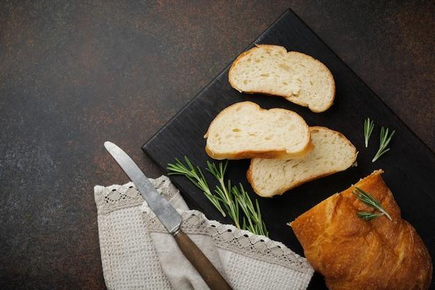 Pão italiano tradicional ciabatta com alecrim em superfície de concreto escuro