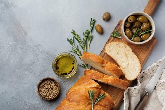 Pão italiano tradicional ciabatta com azeitonas, azeite, pimenta e alecrim em superfície de concreto cinza claro