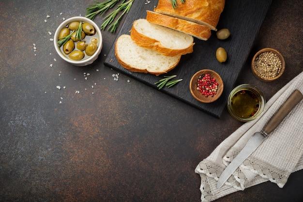 Pão italiano tradicional ciabatta com azeitonas, azeite, pimenta e alecrim em uma superfície de concreto escuro