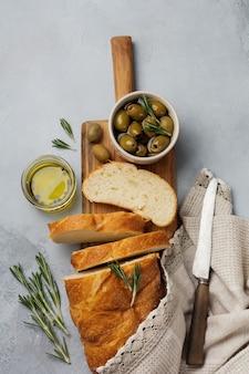 Pão italiano tradicional ciabatta com azeitonas, azeite, pimenta e alecrim em uma superfície de pedra cinza claro