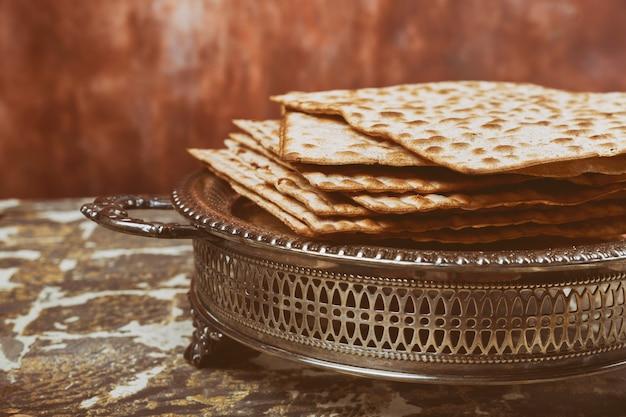 Pão judaico do feriado do matzoh do fundo da páscoa judaica sobre a placa de madeira.