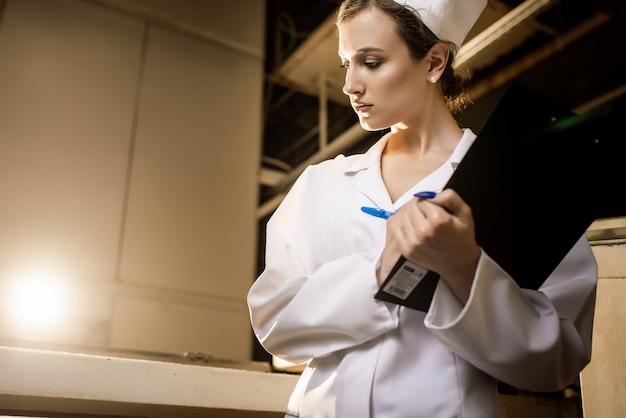 Pão. linha de produção de pão. mulher de uniforme. verificação sanitária.