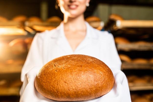 Pão. linha de produção de pão. pão na mão da mulher.