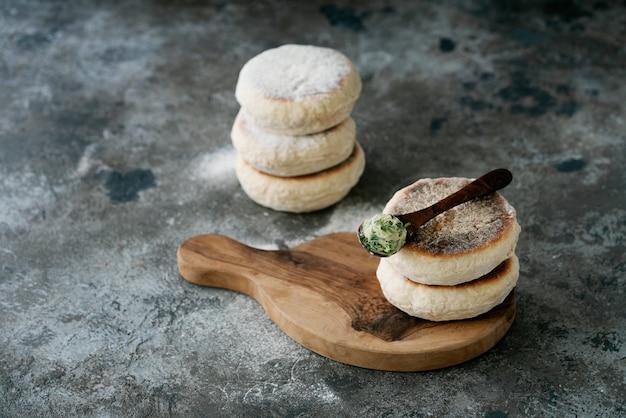 Pão liso circular tradicional português bolo do caco. colher de manteiga de alho com verduras por cima. cozinha da ilha da madeira.