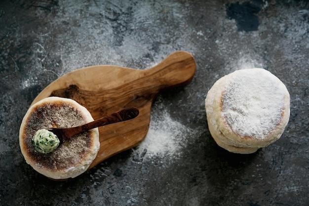 Pão liso circular tradicional português bolo do caco. colher de manteiga de alho com verduras por cima. vista do topo