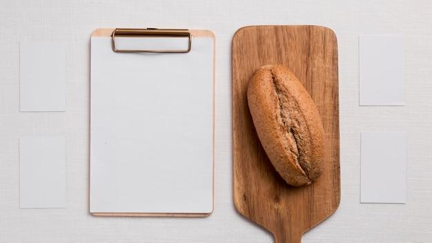 Pão liso na tábua com prancheta em branco