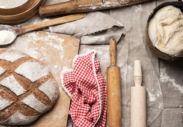 Pão, massa amassada de farinha de trigo branca encontra-se em um balde de metal e um rolo de madeira, vista superior