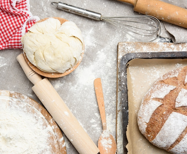 Pão, massa amassada de farinha de trigo branca repousa sobre uma placa de madeira e um rolo de madeira, vista superior