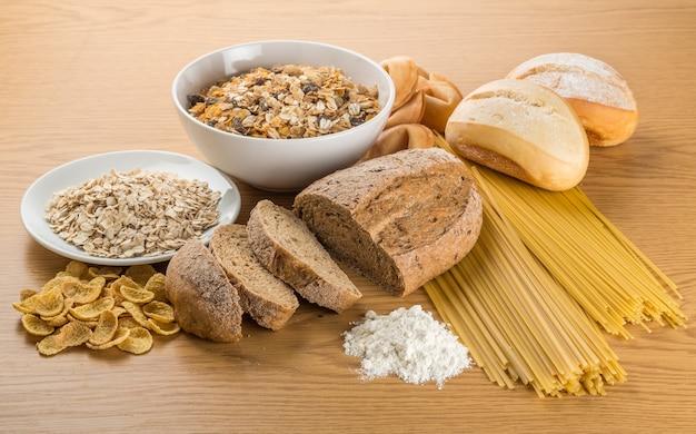 Pão, massa crua, arroz e granola na mesa de madeira