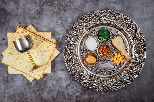 Pão matzah judaico com taça de prata e flores sobre fundo rústico de madeira. conceito de feriado da páscoa
