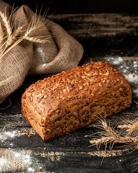 Pão multigrain com farinha e trigo na mesa