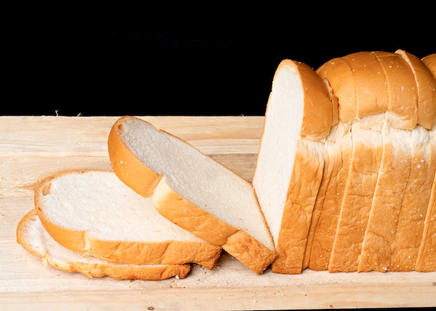 Pão na chapa de madeira no fundo preto