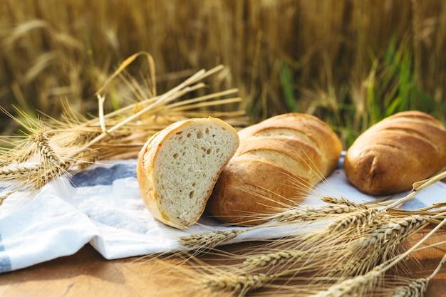 Pão na mesa e trigo no campo de trigo e dia ensolarado