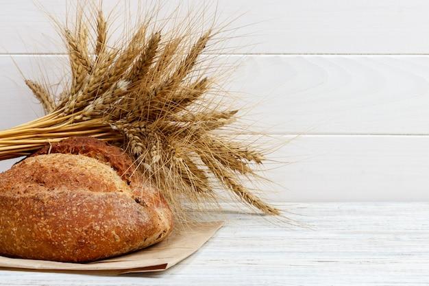 Pão na mesa, pão caseiro com trigo em um fundo de madeira