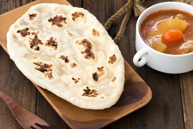 Pão naan de alho indiano na madeira