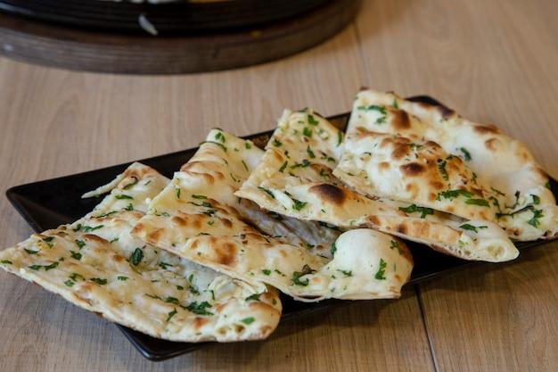 Pão naan indiano com manteiga de alho na mesa de madeira