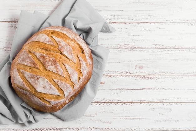 Pão no pano de cozinha e vista superior do plano de fundo de madeira