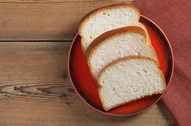 Pão no prato vermelho na mesa de madeira, vista superior