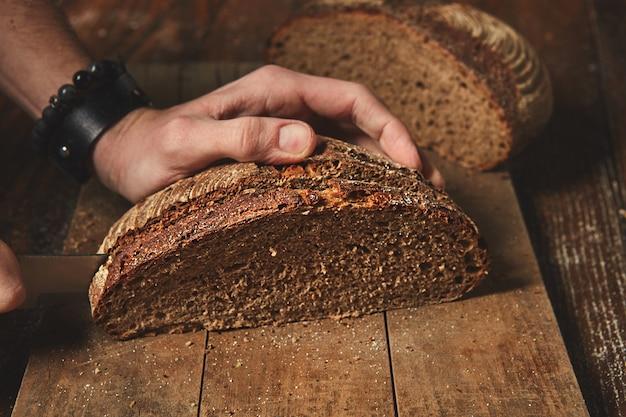 Pão orgânico fresco em uma placa de madeira cortado nas mãos de um homem