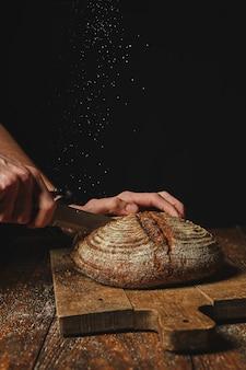 Pão orgânico fresco em uma placa de madeira cortou as mãos de um homem