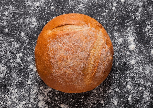 Pão orgânico sem glúten recém-assados com farinha no fundo preto