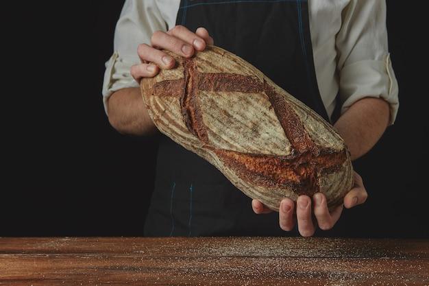 Pão oval orgânico fresco nas mãos de um padeiro em um fundo preto de uma mesa de madeira