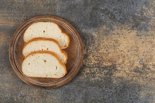 Pão perfumado fatiado em tábua de madeira