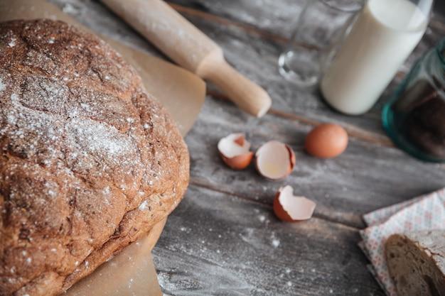 Pão perto de ovos e leite na mesa.