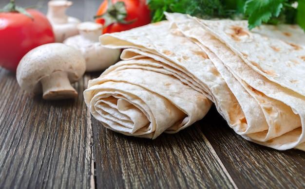 Pão pita fino com legumes frescos em um fundo de madeira.
