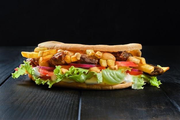 Pão pitta recheado com salada, tomate, cebola, batata frita e cordeiro