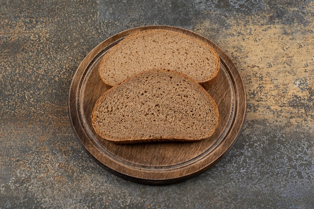 Pão preto caseiro na placa de madeira.