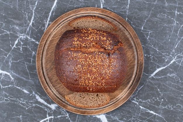 Pão preto com gergelim no prato de madeira, na superfície de mármore