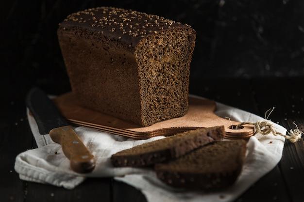 Pão preto com sementes de alcaravia, fatias leigos em uma placa de madeira