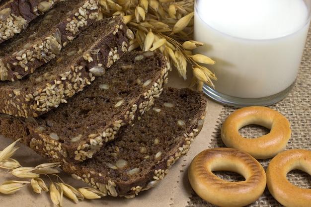Pão preto com sementes de gergelim e sementes de girassol, aveia, espigas de trigo, um copo de leite