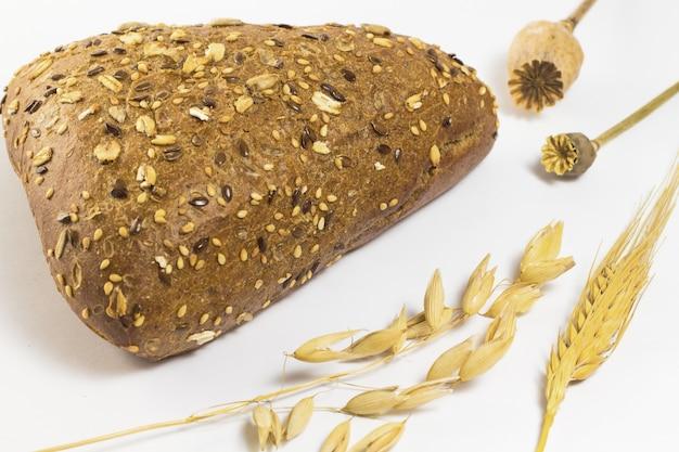 Pão preto com sementes de gergelim e sementes de girassol. cevada e aveia galhos. duas papoulas